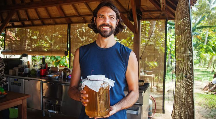 Man holding a jar of Kombucha Tea