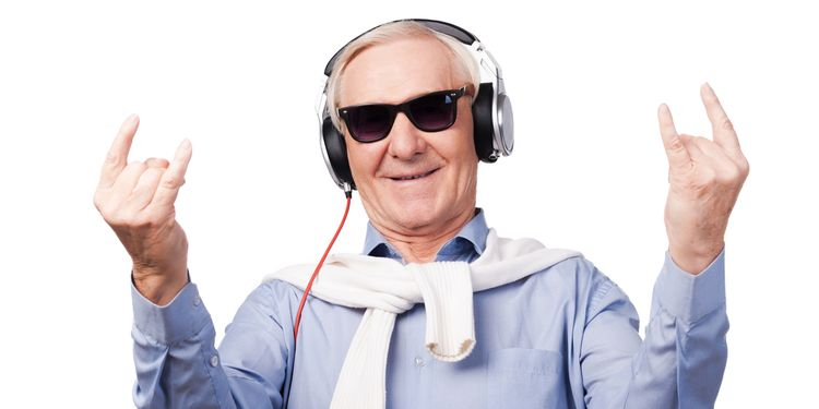 Forever young. Cheerful senior man in headphones listening to music and showing hand sign while standing against white background
