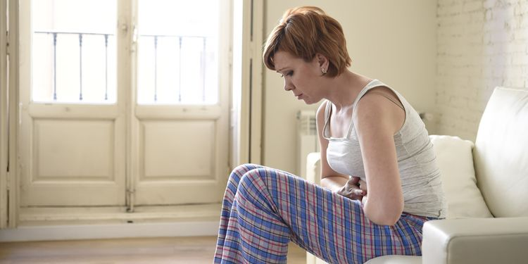 Photo of a woman suffering stomach cramp and period pain sitting on home couch
