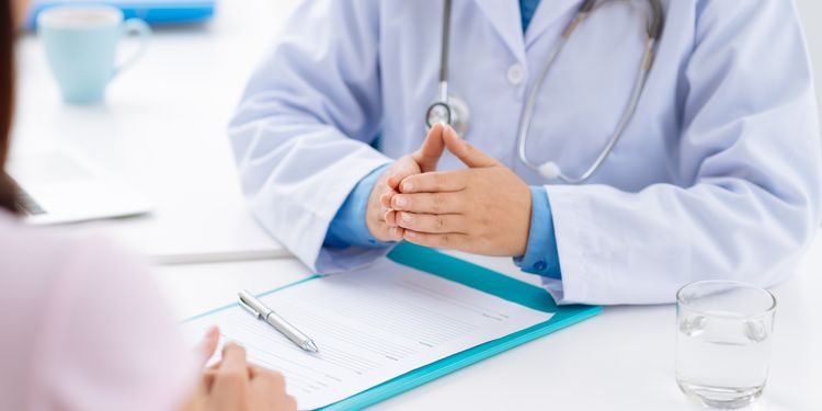Cropped image of doctor informing female patient of diagnosis