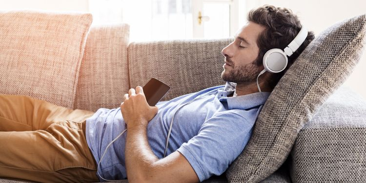 Photo of a man lying on couch listening relaxing music