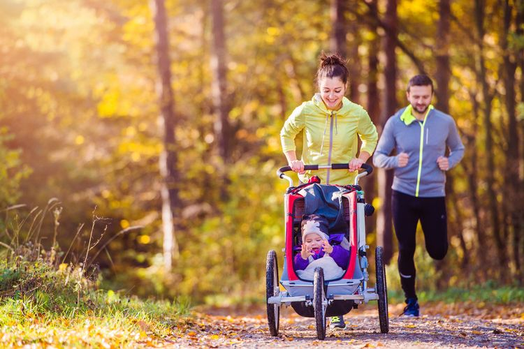 Photo of a Beautiful young family running outside in autumn nature