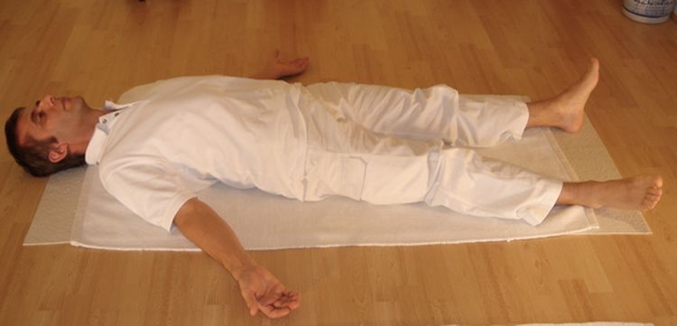 Photo of a man laying in a shavashana yoga pose
