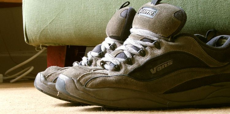 Photo of old smelly sport shoes next to sofa on floor