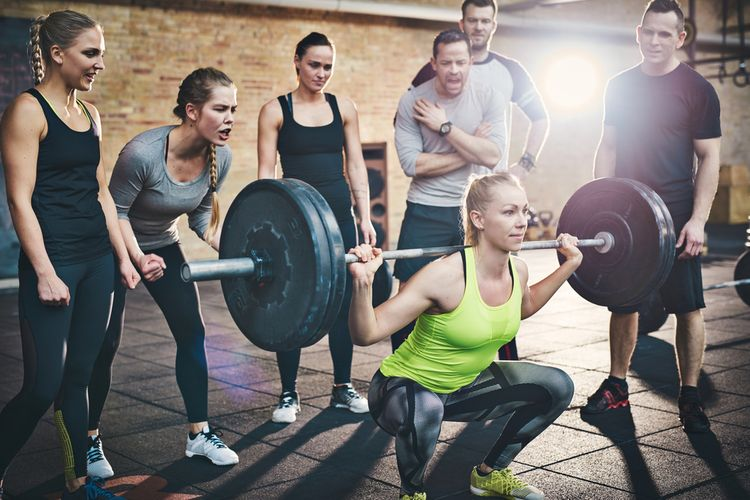 Photo of a girl squatting at a gym sorrounded by her colleagues