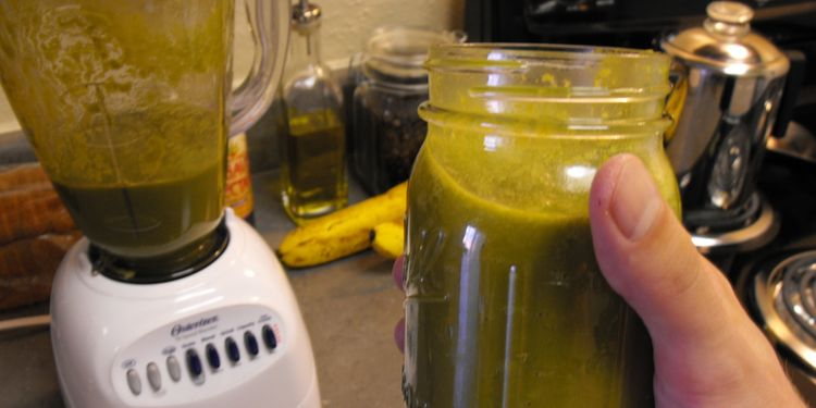 Photo of jar full of stomach aid smoothie held in hand next to a blender