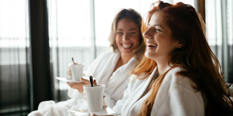Photo of happy women in bathrobes enjoying tea during wellness weekend