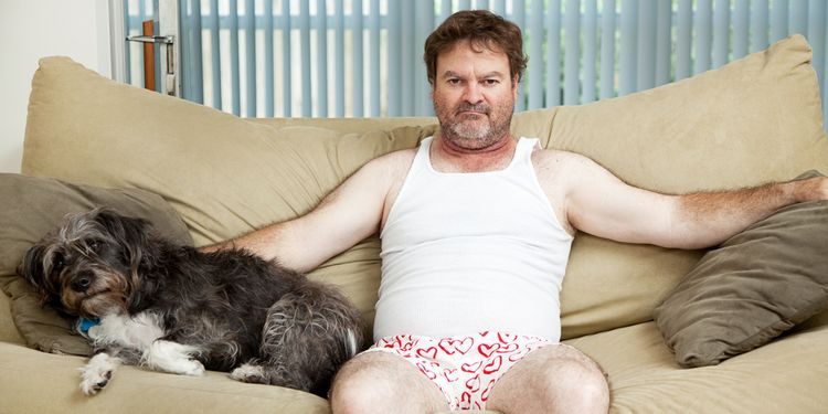 Photo of an angry man with dog sitting on a couch in underwear