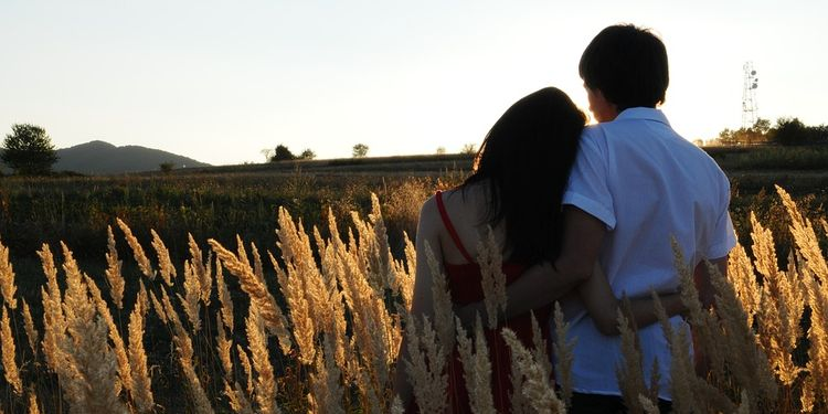 Photo of couple hugging in tall grass