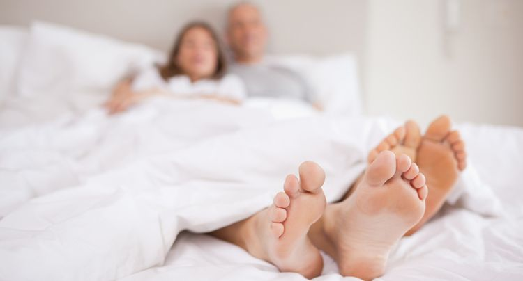 Photo of couple lying in a bed with the camera focus on their feet