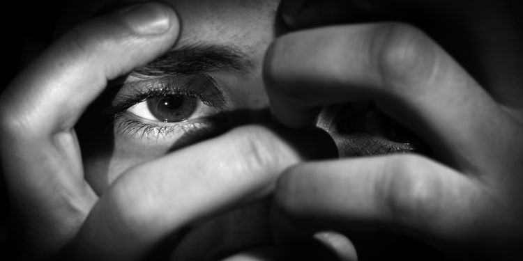 Photo of a woman showing her eye through her hands with an disturbing attitude