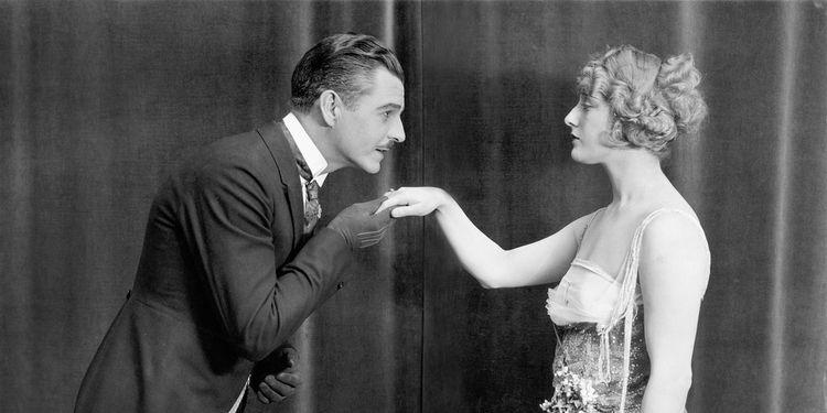 Old black and white photo of gentleman kissing lady's hand