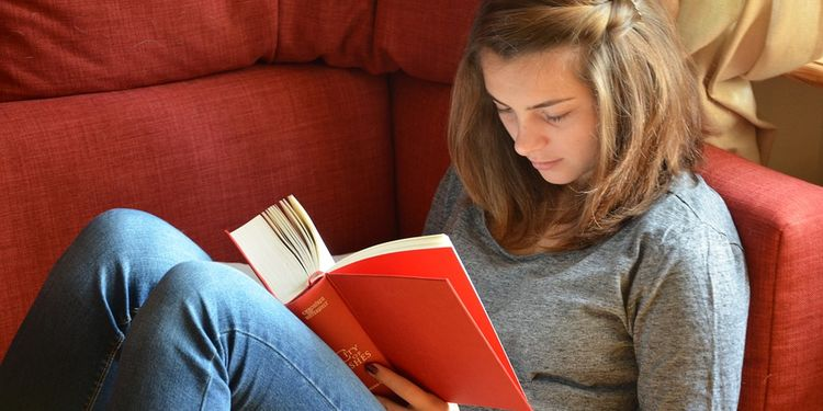 Photo of a girl sitting on a couch reading a red book