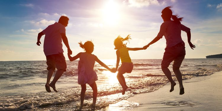Photo of happy couple with kids on beach