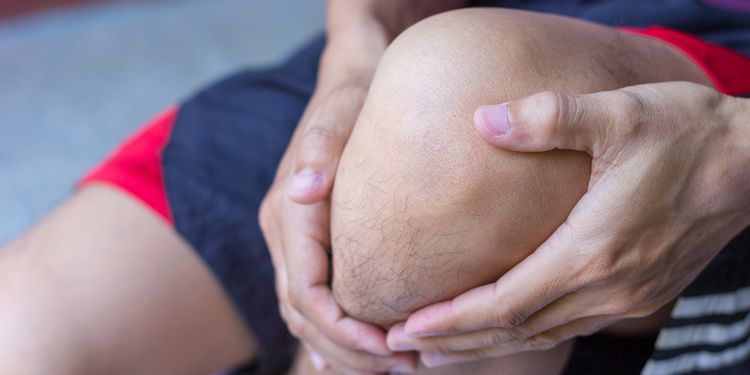 Photo close up of a man holding the painful knee