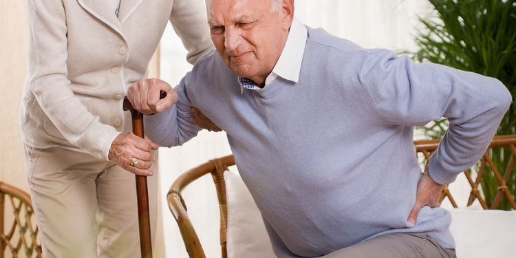 Photo of woman helping an elderly man having a back pain