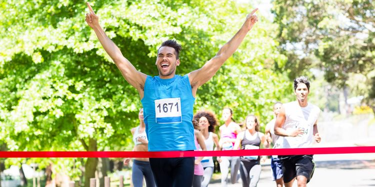 Photo of an excited male runner crossing the finshline of a marathon