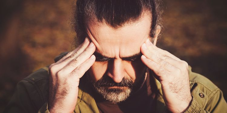 Photo of a man with headache holding his head with his hands