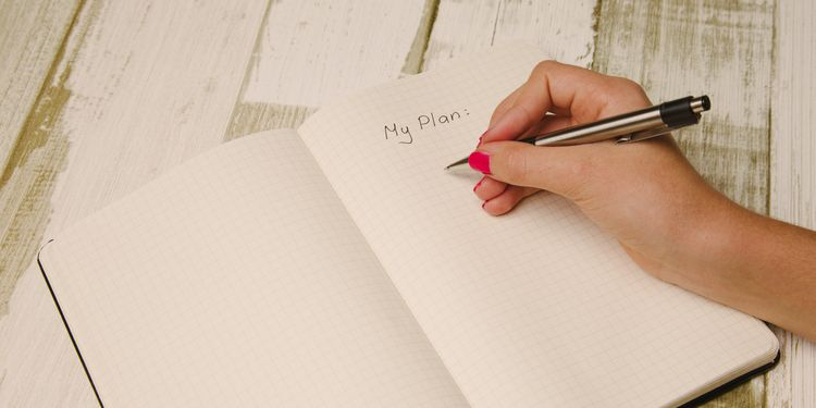 Photo of a female hand holding a pen and writing a plan in a planner