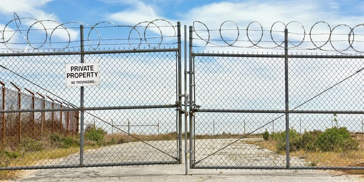 Photo of gateway with private property notice and barbed wire above