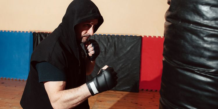 Photo of a Man training with punching bag at gym