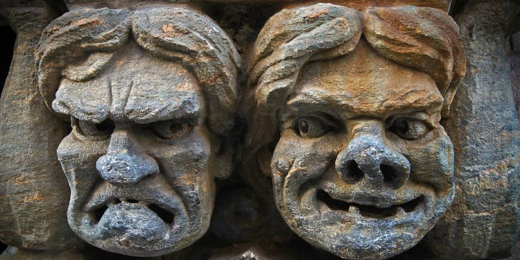 Photo of a stonewall carvings showing tragedy and comedy faces