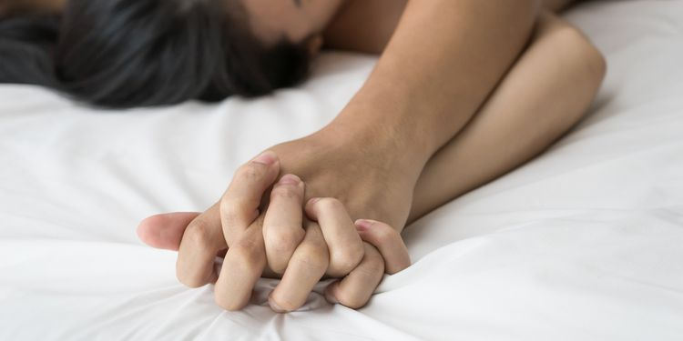 Photo of young couple making love in bed focus on hand