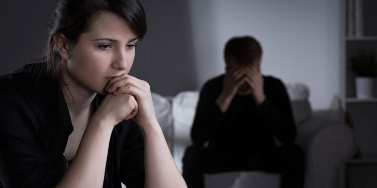 Photo of worried young couple in dark room