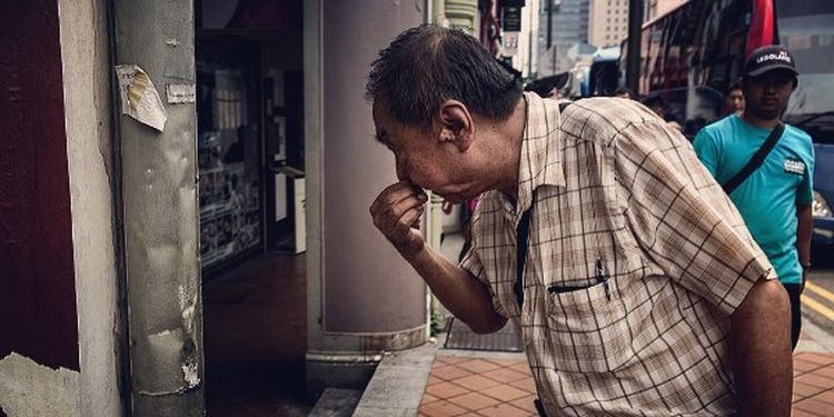 Image of an oldman blowing his nose