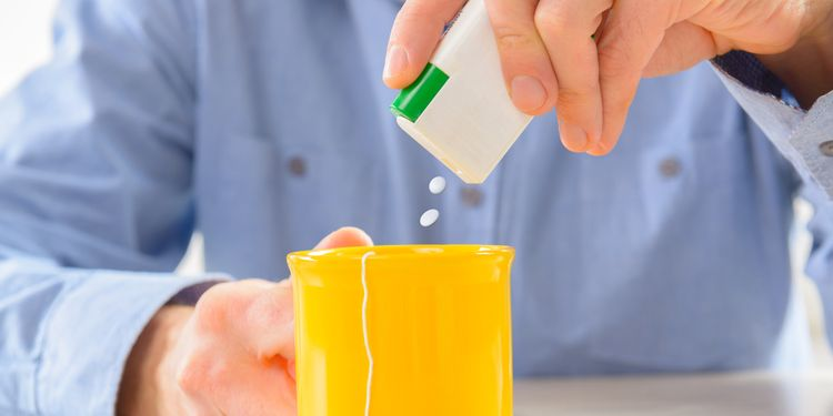 Photo of a man using aspartame artificial sweetener