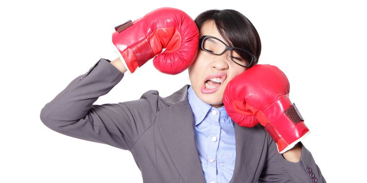 Photo of Asian girl with glasses kicking herself with boxing gloves