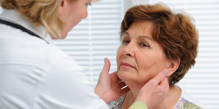 Photo of a woman at doctors office examining the thyroid gland