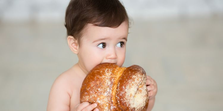 Photo of baby biting a piece of bread