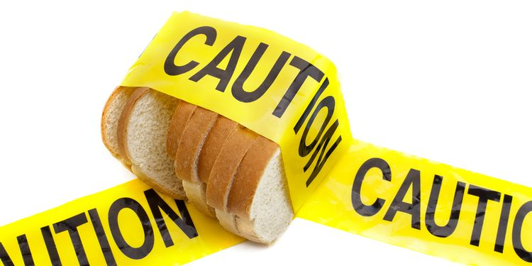 Photo of a white bread slices in yellow tape saying CAUTION