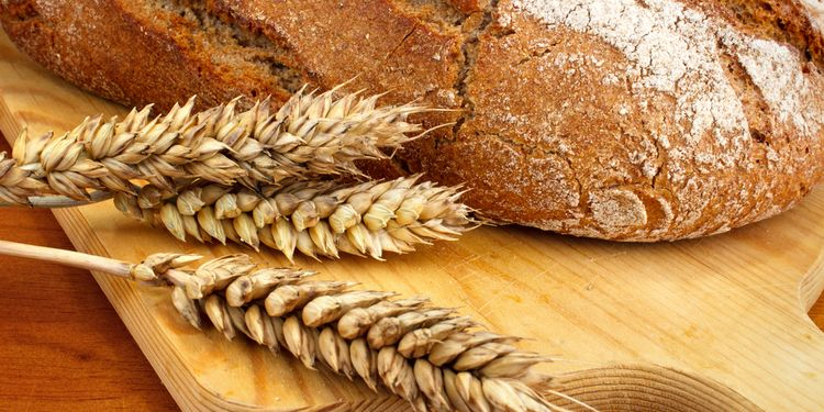 Photo of bread with wheat next to it
