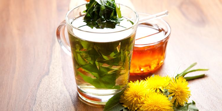 Photo of herbal tea and a dandelion flowers on table
