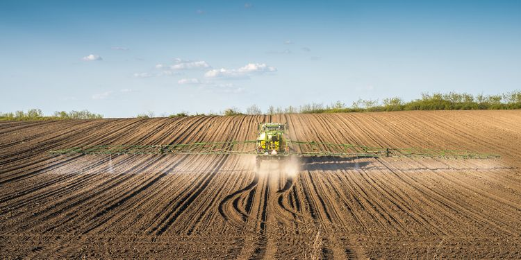 Photo of tractor in field spraying pesticides