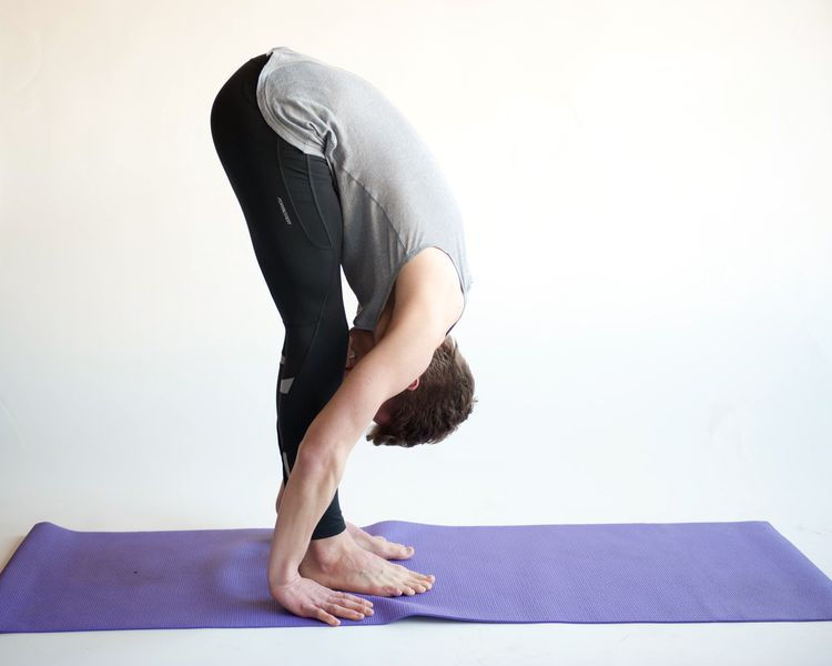 Photo of a man performing standing forward bend yoga pose