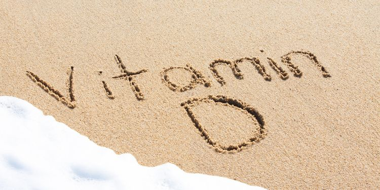 Photo of vitamin D word written on beach sand