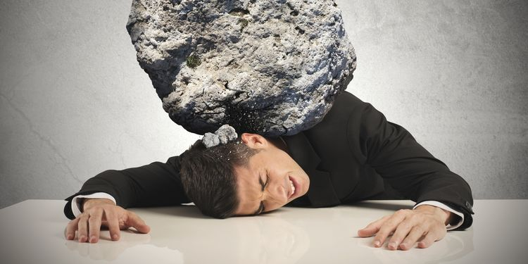 Photo of a businessman with large rock on his back