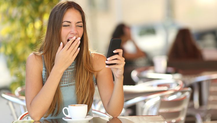Photo of a girl drinking coffee and yawning