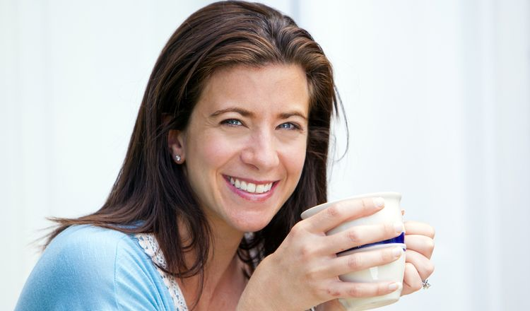 Photo of smiling woman drinking coffee