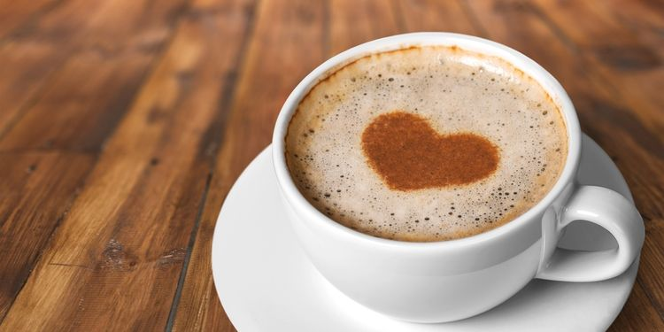 Photo of coffee cup with cream making heart shape