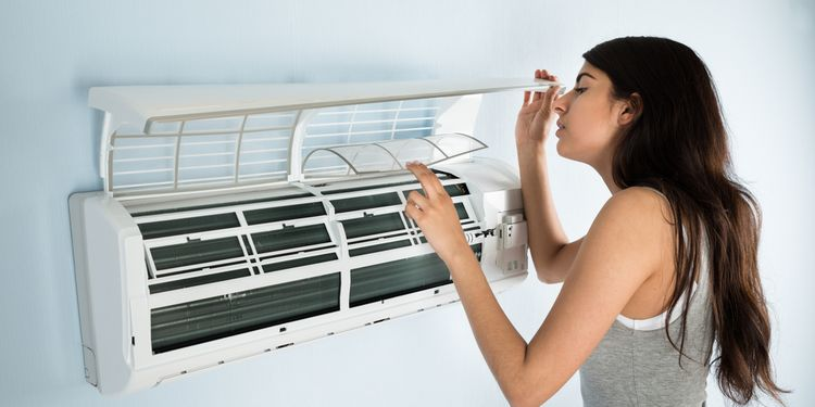 Photo of a woman cleaning dirty AC filter