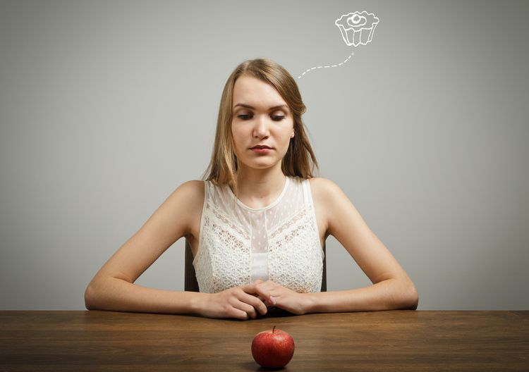 Photo of a woman thinking on cake looking at an apple