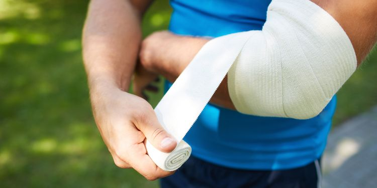 Photo of a man bandaging his elbow