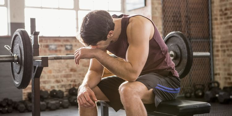 Photo of exhausted man in gym