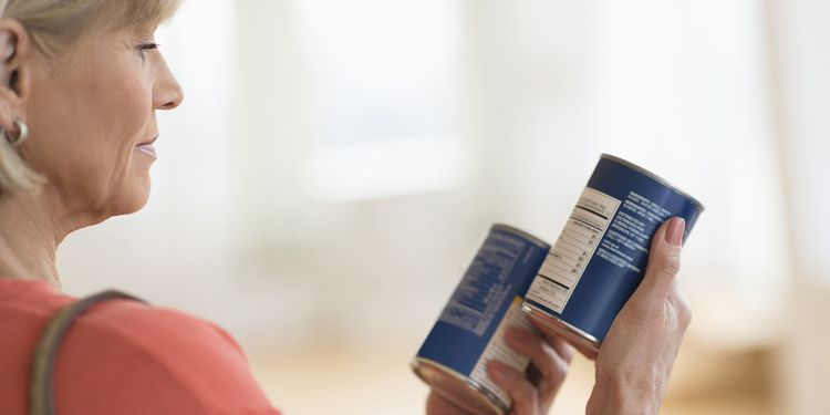 Photo of lady looking at the food labels on a can