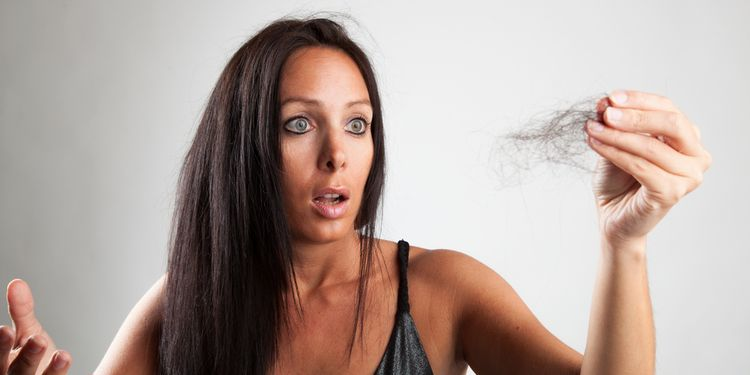 Photo of woman holding her lost hair