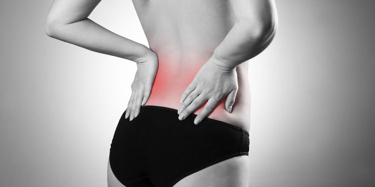 Photo of woman holding her lower back region in pain